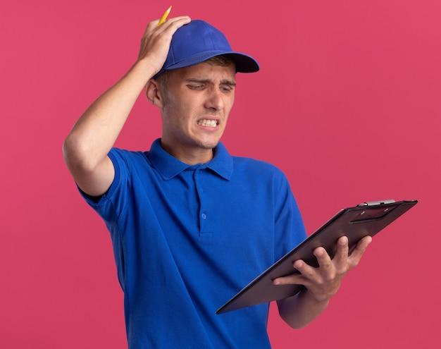 Trauriger junger blonder lieferjunge legt hand auf kopf, der zwischenablage auf rosa hält und betrachtet