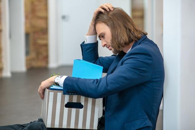Trauriger junger erwachsener mann im anzug sitzend mit kasten auf boden drinnen, der hand auf kopf hält