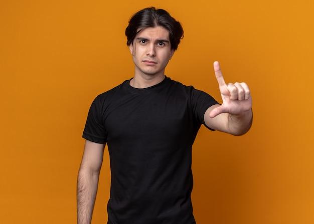 Trauriger junger gutaussehender kerl, der ein schwarzes t-shirt trägt und eine verlierergeste zeigt, die auf oranger wand isoliert ist?