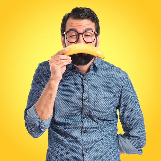 Trauriger junger hipstermann mit banane auf buntem hintergrund