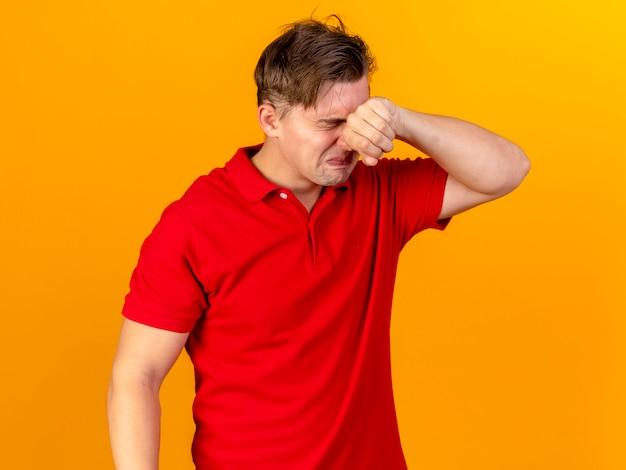 Trauriger junger hübscher blonder kranker mann, der weint und tränen mit geschlossenen augen wischt, die auf orange wand lokalisiert werden