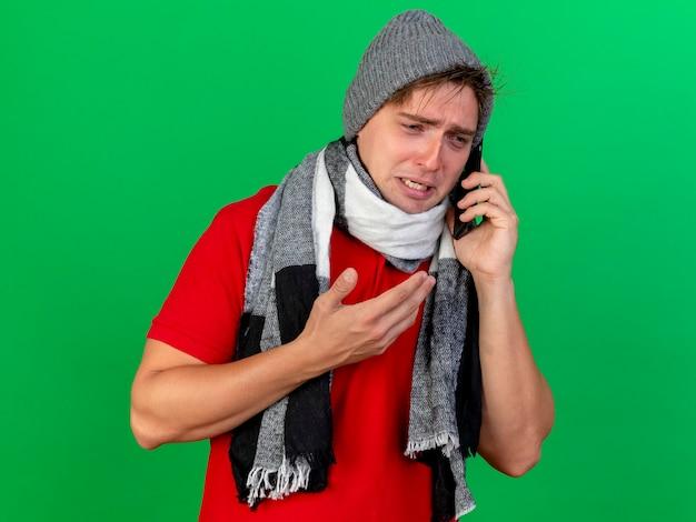 Trauriger junger hübscher blonder kranker mann, der wintermütze und schal trägt, die am telefon sprechen, das die seite hält, die hand in der luft lokalisiert auf grünem hintergrund mit kopienraum hält