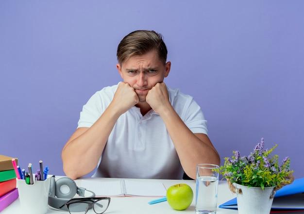 Trauriger junger hübscher männlicher student, der am schreibtisch mit schulwerkzeugen sitzt, die fäuste auf kinn lokalisiert auf blau setzen
