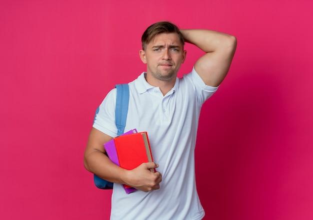 Trauriger junger hübscher männlicher student, der rückentasche hält bücher hält