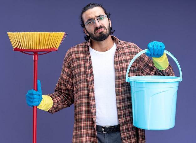 Trauriger junger hübscher reinigungsmann, der t-shirt und handschuhe hält eimer mit mopp lokalisiert auf blauer wand trägt