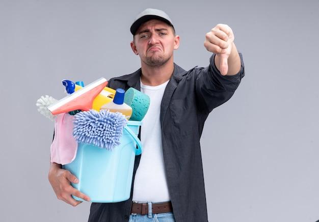 Trauriger junger hübscher reinigungsmann, der t-shirt und kappe hält, die eimer mit reinigungswerkzeugen hält, der daumen unten lokalisiert auf weißer wand zeigt