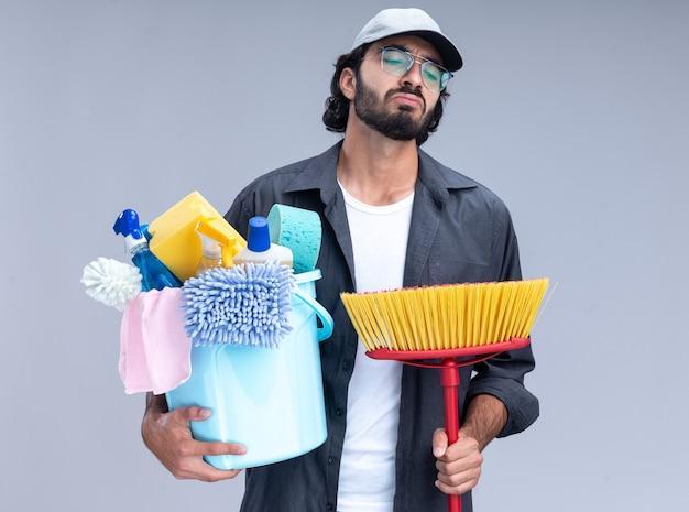Trauriger junger hübscher reinigungsmann, der t-shirt und kappe hält eimer mit reinigungswerkzeugen mit mopp lokalisiert auf weißer wand trägt
