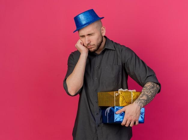 Trauriger junger hübscher slawischer party-typ, der partyhut hält, der geschenkpackungen und und papiertüten lokalisiert auf purpurrotem hintergrund mit kopienraum hält