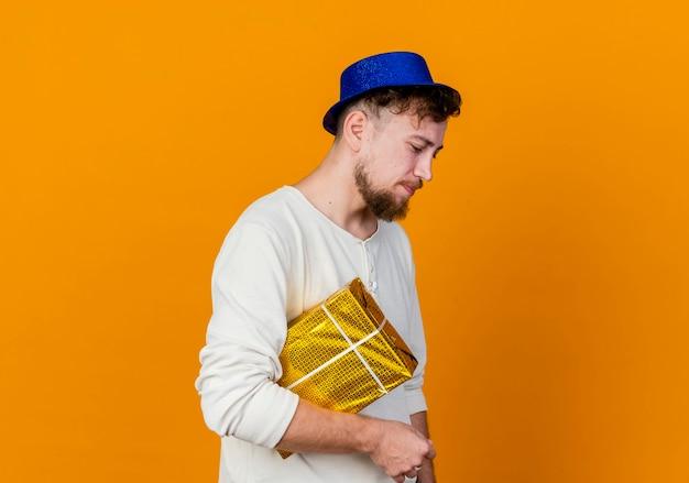 Trauriger junger hübscher slawischer party-typ, der partyhut trägt, der in der profilansicht hält geschenkbox hält, die lokalisiert auf orange hintergrund mit kopienraum schaut