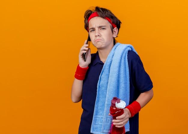 Trauriger junger hübscher sportlicher junge mit handtuch auf schulter, wasserflasche haltend und am telefon sprechend
