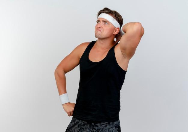 Trauriger junger hübscher sportlicher mann, der stirnband und armbänder trägt, die seite betrachten hände auf taille und hinter kopf lokalisiert auf weißer wand