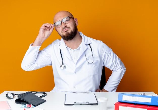 Trauriger junger kahlköpfiger männlicher arzt, der medizinische robe und stethoskop trägt, die am schreibtisch mit medizinischen werkzeugen sitzen, nehmen brille auf orange auf