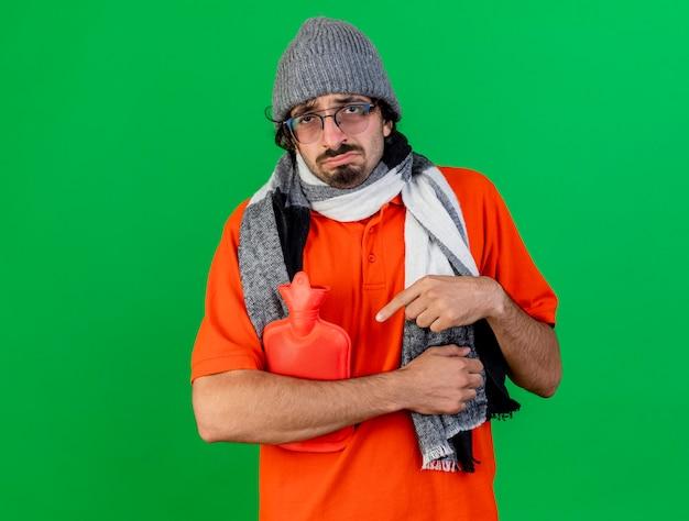 Trauriger junger kaukasischer kranker mann, der brillenwintermütze und -schal hält und auf heißwassersack zeigt, der kamera lokalisiert auf grünem hintergrund mit kopienraum betrachtet