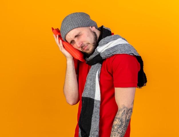 Trauriger junger kaukasischer kranker mann, der wintermütze und schal trägt, setzt kopf auf wärmflasche lokalisiert auf orange wand mit kopienraum