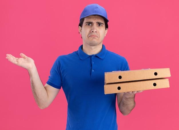 Trauriger junger kaukasischer lieferbote in blauer uniform und mütze mit pizzapaketen, die leere hand zeigen