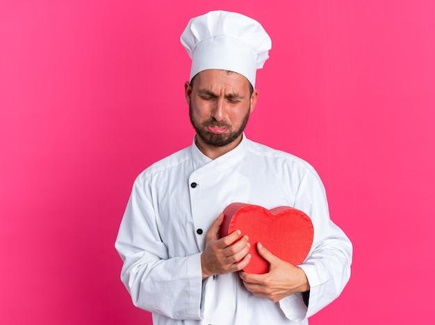 Trauriger junger kaukasischer männlicher koch in kochuniform und mütze, die herzform hält und mit geschlossenen augen weint, isoliert auf rosa wand