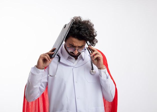 Trauriger junger kaukasischer superheldenmann in der optischen brille, die arztuniform mit rotem umhang und mit stethoskop um hals trägt, hält klemmbrett und bleistift am kopf mit kopienraum