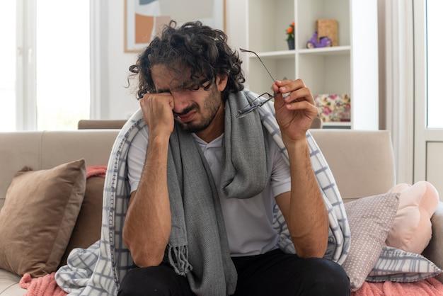 Trauriger junger kranker kaukasischer mann, der in plaid mit schal um den hals gehüllt ist, wischt sich die tränen ab und hält eine optische brille auf der couch im wohnzimmer sitzen?