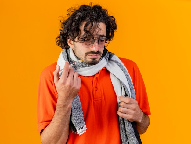 Trauriger junger kranker mann, der brille und schal hält, die spritze und ampulle halten, betrachten ampulle lokalisiert auf orange wand