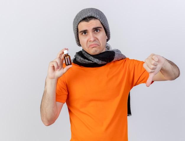 Trauriger junger kranker mann, der wintermütze mit schal hält medizin in der glasflasche zeigt daumen unten
