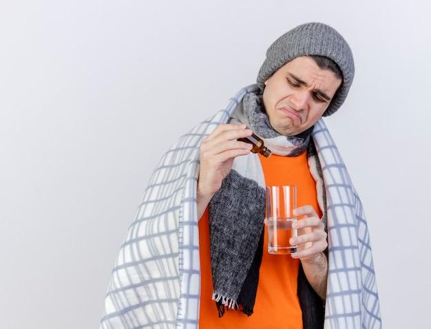 Trauriger junger kranker mann, der wintermütze mit schal trägt, der in plaid eingewickelt wird, das medikament in glas wasser gießt