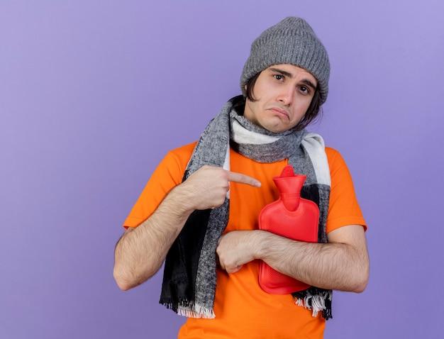 Trauriger junger kranker mann, der wintermütze mit schal umarmt und punkte auf heißwassersack lokalisiert auf lila hintergrund trägt