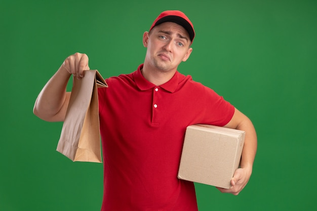 Trauriger junger lieferbote, der uniform und kappe hält, die papiernahrungsmittelpaket mit kasten lokalisiert auf grüner wand hält