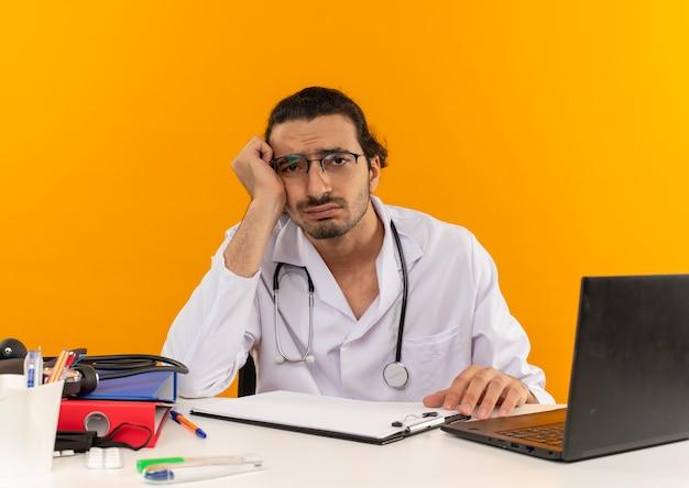 Trauriger junger männlicher arzt mit medizinischer brille, die medizinische robe mit stethoskop sitzend trägt