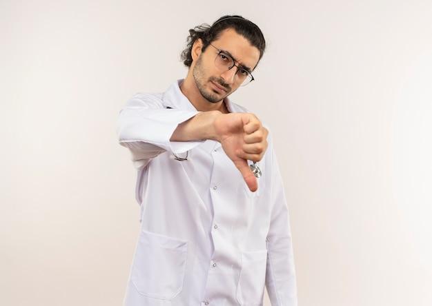 Trauriger junger männlicher arzt mit optischer brille, die weiße robe mit stethoskop seinen daumen nach unten trägt