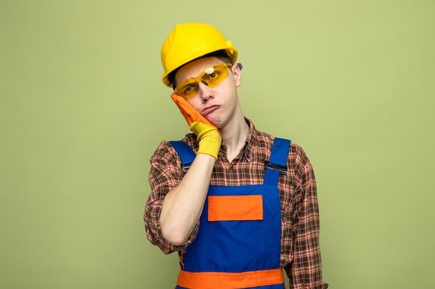 Trauriger junger männlicher baumeister, der uniform und handschuhe mit brille trägt