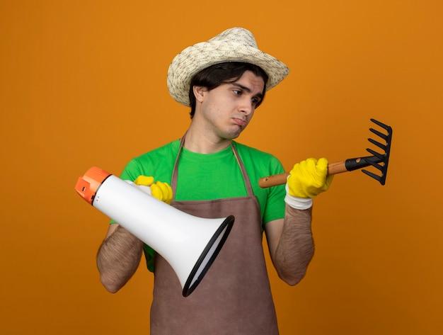 Trauriger junger männlicher gärtner in der uniform, die gartenhut mit handschuhen hält, die lautsprecher halten und rechen in seinem handrechen lokalisiert auf orange betrachten