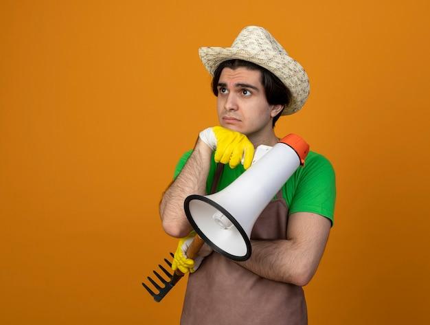 Trauriger junger männlicher gärtner in der uniform, die gartenhut mit handschuhen trägt, die seite betrachten, die lautsprecher mit rechen hält, der hand unter kinn legt