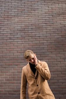 Trauriger junger mann. besorgter besiegter ausdruck. verzweiflung emotionen. hand im gesicht. raumkonzept kopieren