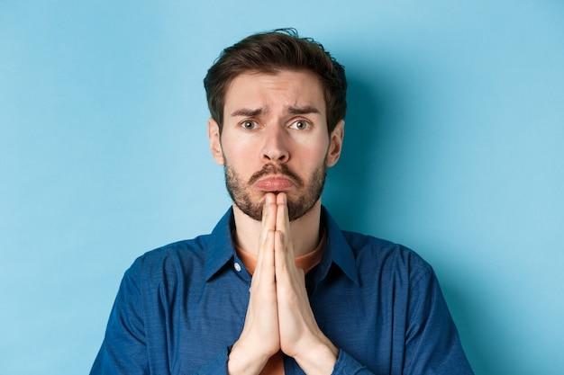 Trauriger junger mann, der um hilfe bettelt, apoligisiert und elend schluchzt, auf blauem hintergrund stehend.