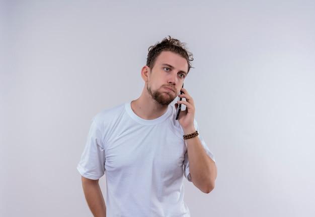 Trauriger junger mann, der weißes t-shirt trägt, spricht am telefon auf lokalem weißem hintergrund