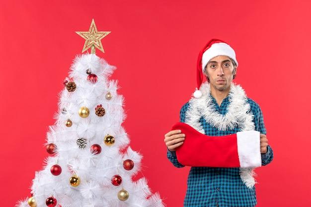 Trauriger junger mann mit weihnachtsmannhut in einem blau gestreiften hemd und weihnachtssocke nahe weihnachtsbaum auf rot