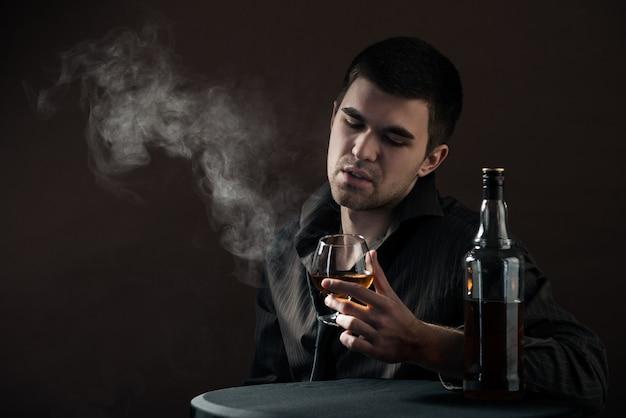 Trauriger junger mann schlägt ein alkoholisches getränk von einem huhn, das in einem dunklen raum sitzt