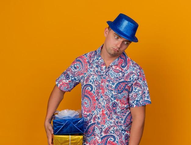 Trauriger junger party-typ, der blauen hut hält, der geschenkbox lokalisiert auf orange hält