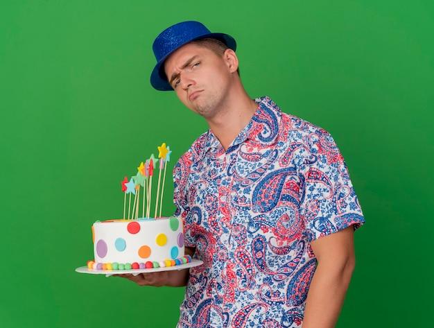 Trauriger junger party-typ, der blauen hut hält kuchen lokalisiert auf grün