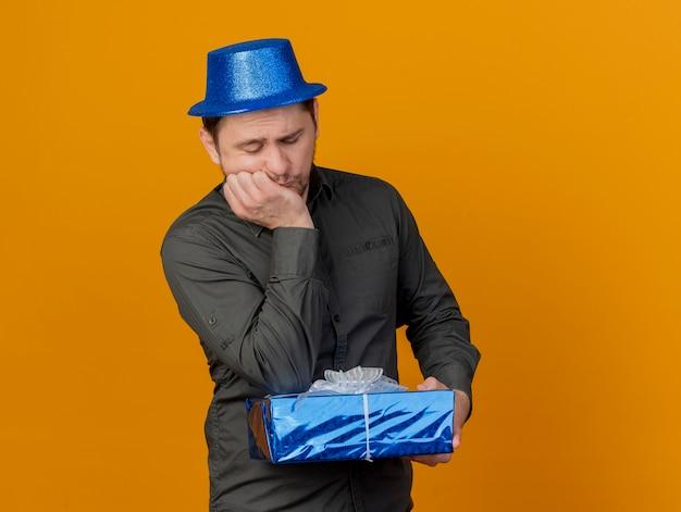 Trauriger junger party-typ, der blauen hut hält und ellbogen auf geschenkbox lokalisiert auf orange setzt