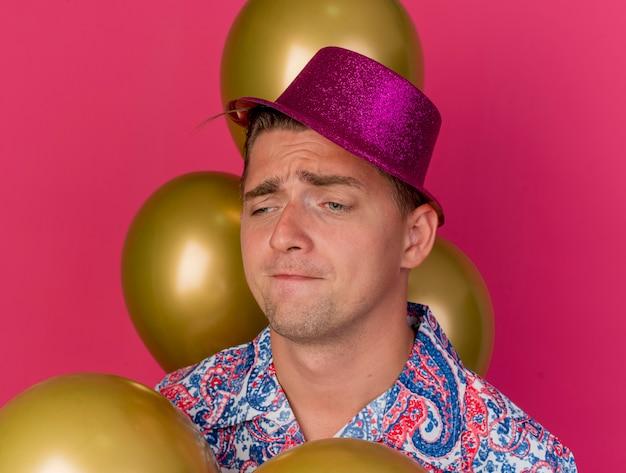Trauriger junger party-typ, der rosa hut trägt, der unter den auf rosa isolierten luftballons steht
