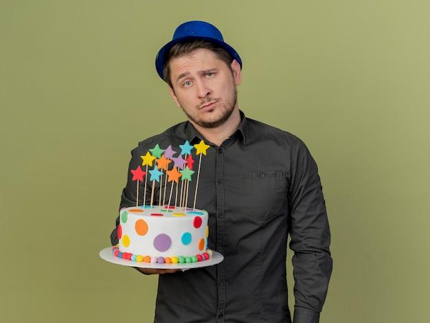 Trauriger junger party-typ, der schwarzes hemd und blauen hut hält, der kuchen lokalisiert auf olivgrün hält