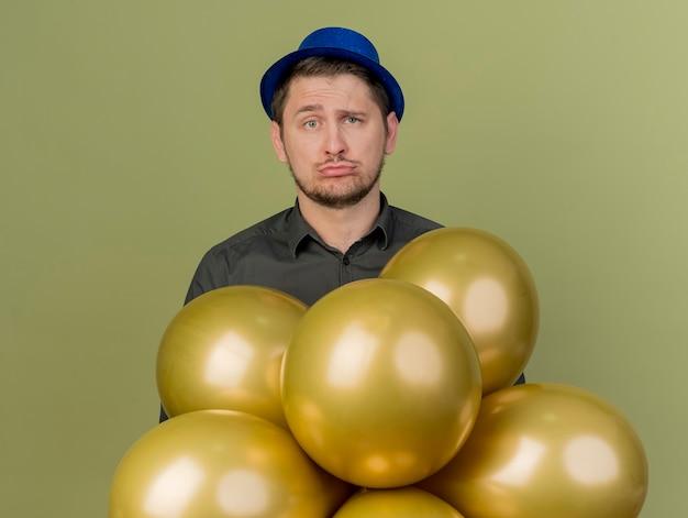 Trauriger junger party-typ, der schwarzes hemd und blauen hut trägt, der hinter luftballons steht, die auf olivgrün isoliert werden