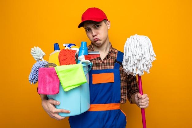 Trauriger junger putzmann in uniform und mütze, der einen eimer mit reinigungswerkzeugen mit mopp hält