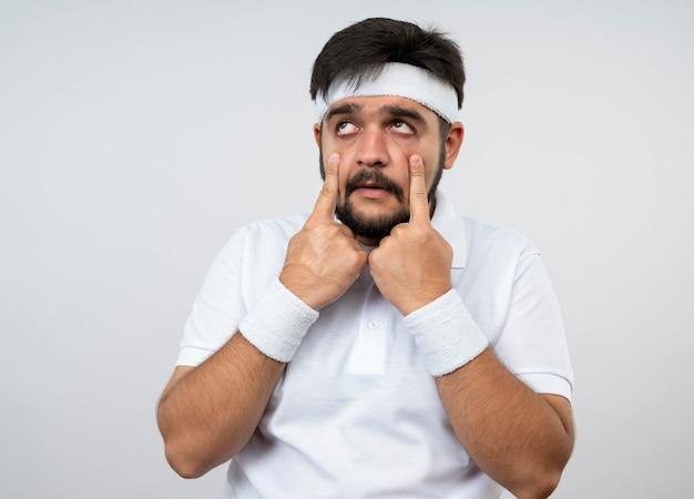 Trauriger junger sportlicher mann, der seitliches tragen des stirnbandes und des armbandes betrachtet, die augenlider ziehen, lokalisiert auf weißer wand