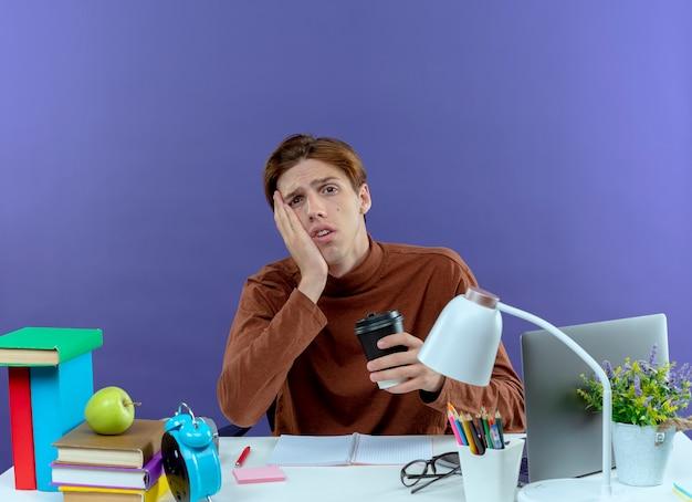 Trauriger junger studend junge, der am schreibtisch mit schulwerkzeugen sitzt, die tasse kaffee halten, die hand auf wange auf lila hält