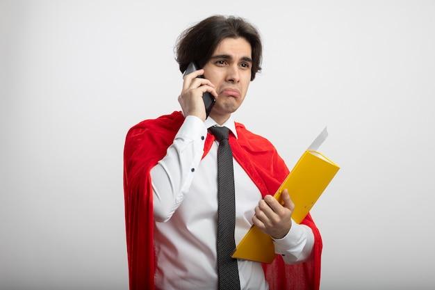 Trauriger junger superheld kerl, der seite sieht, die krawattenhalter hält und am telefon isoliert auf weiß spricht