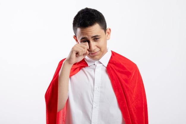 Trauriger junger superheldenjunge im roten umhang, der unten wischendes auge mit hand lokalisiert auf weißem hintergrund mit kopienraum schaut
