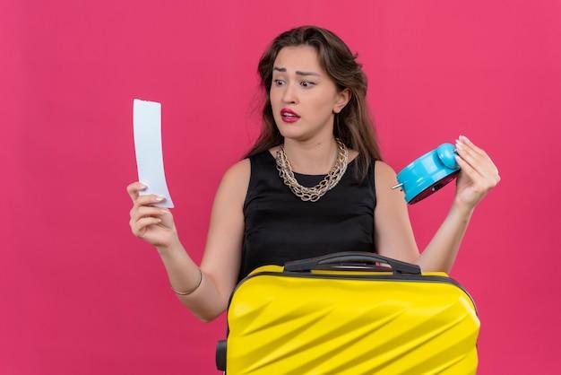 Trauriger junger weiblicher reisender, der schwarzes unterhemd hält wecker und ticket, das ticket auf roter wand betrachtet