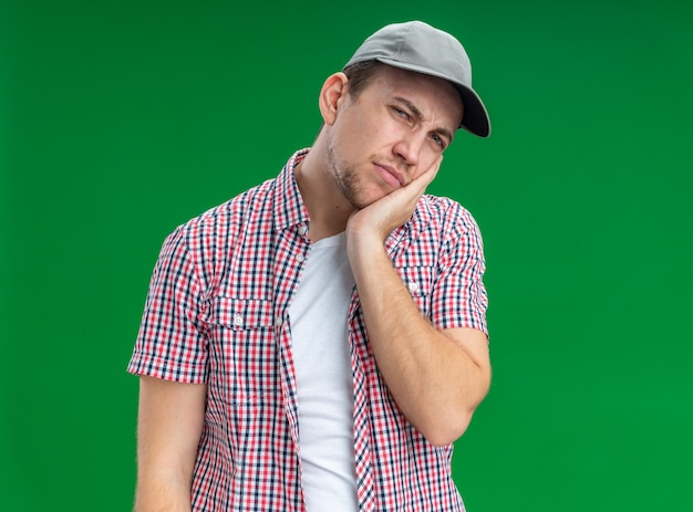 Trauriger, kippender junger kerl, der eine mütze trägt und die hand auf die wange legt, isoliert auf grünem hintergrund